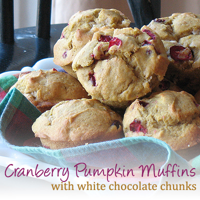Pumpkin cranberry muffins with white chocolate chunks resting in a bowl.