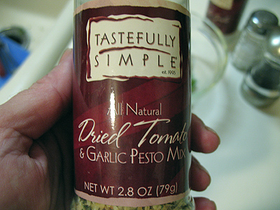 A close up photo of a bottle of dried tomato and garlic pesto mix.