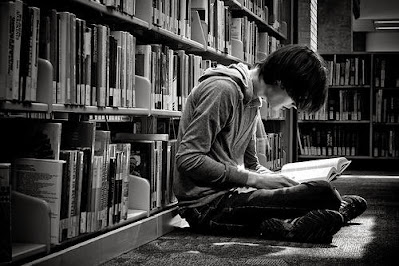Boy sits in between the stacks at a library to read a book.