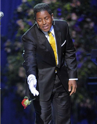 """brother Jermaine tosses a rose onto Michael's casket while singing """"smile"""""""